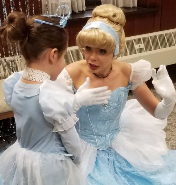 Woman dressed as Disney's Cinderella talking to little girl dressed in princess costume