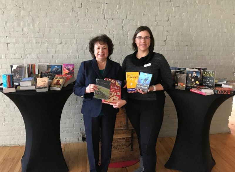 Two women holding books and standing in front of two tables piled with books