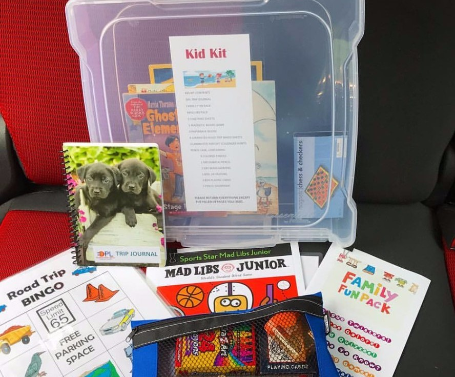 "A container labeled ""Kid Kit"" with Bingo sheets, mad libs, activity books, crayons, games, and more laid out next to the container"