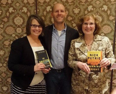 Connie and Laurie standing with author Nick Petrie, holding his books