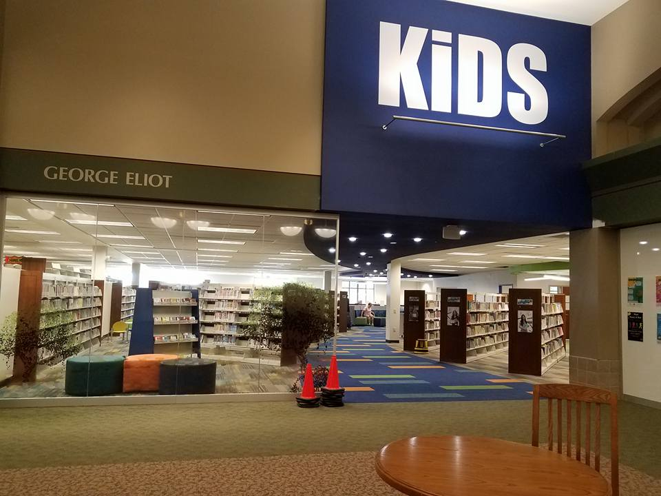 Open area in a library with a large, blue KIDS sign above it
