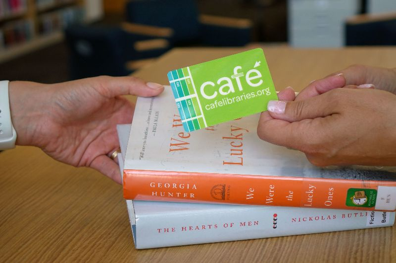 A hand passing a CAFE library card to another hand, over a stack of books