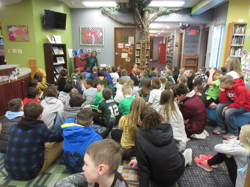 Crowd of children sit on floor facing a person who reads to them from armchair