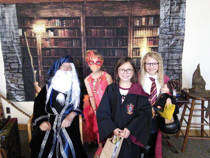 Group of children in wizard costumes standing in front of Hogwarts classroom backdrop