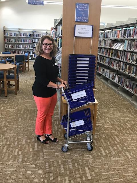Woman stands next to library bookshelf, pushing a cart with blue baskets on it.