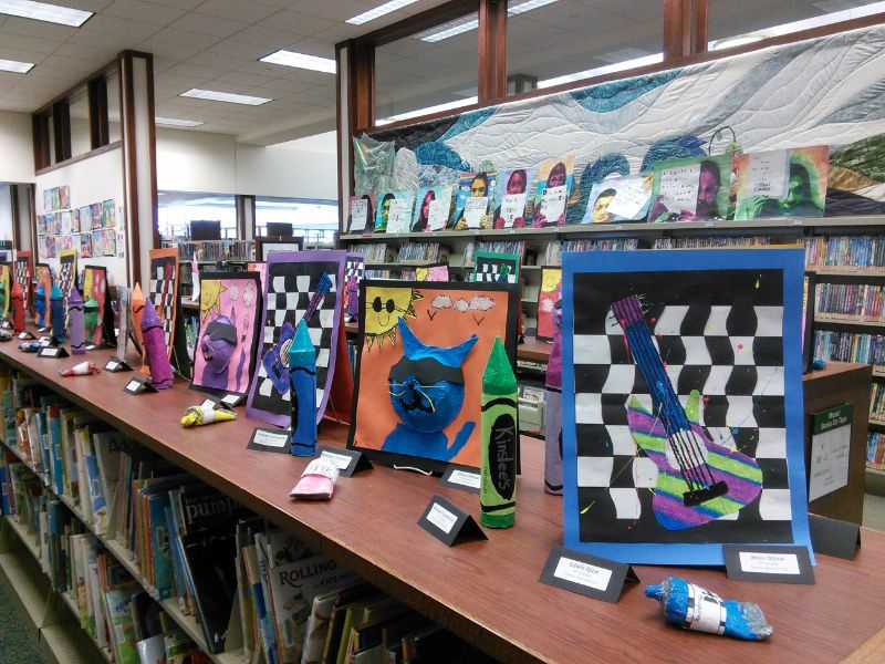 Row of artwork displayed on top of bookshelf in library