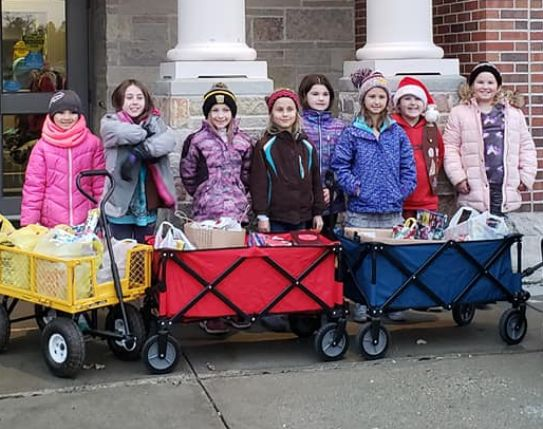Group of girls in winter coats stand behind three wagons full of bags and boxes