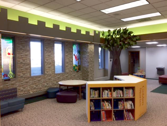 Wall, tree, and bookshelves in the toddler area at Brookfield Public Library