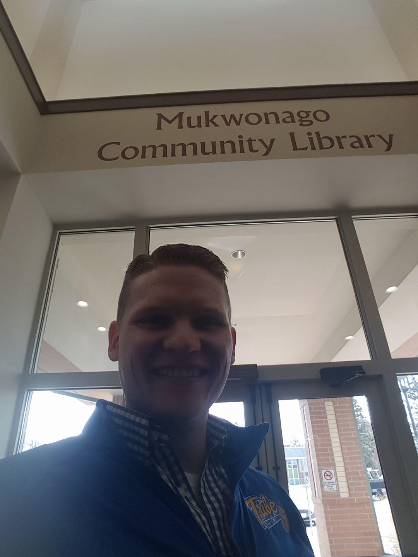 Rep. Cody Horlacher standing under Mukwonago sign at front doors