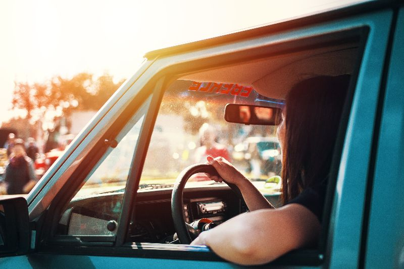 Woman driving blue vehicle with window rolled down