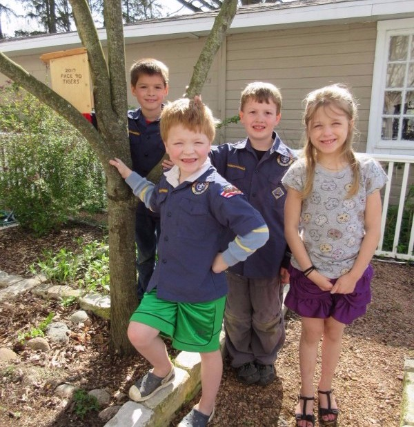 Four kids standing by tree and birdhouse