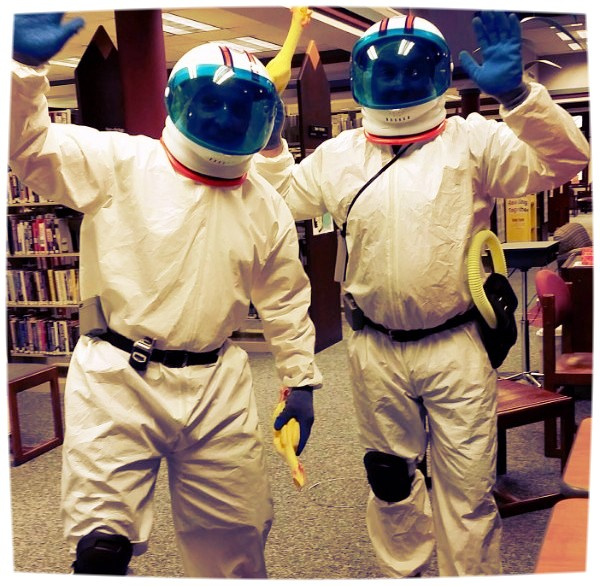 Two men in space suits walking through the library