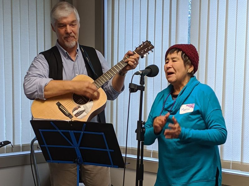 Elderly woman singing into microphone. Man plays guitar behind her.