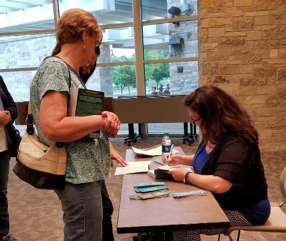 Amy Reichert signing a book at a table while two women look on