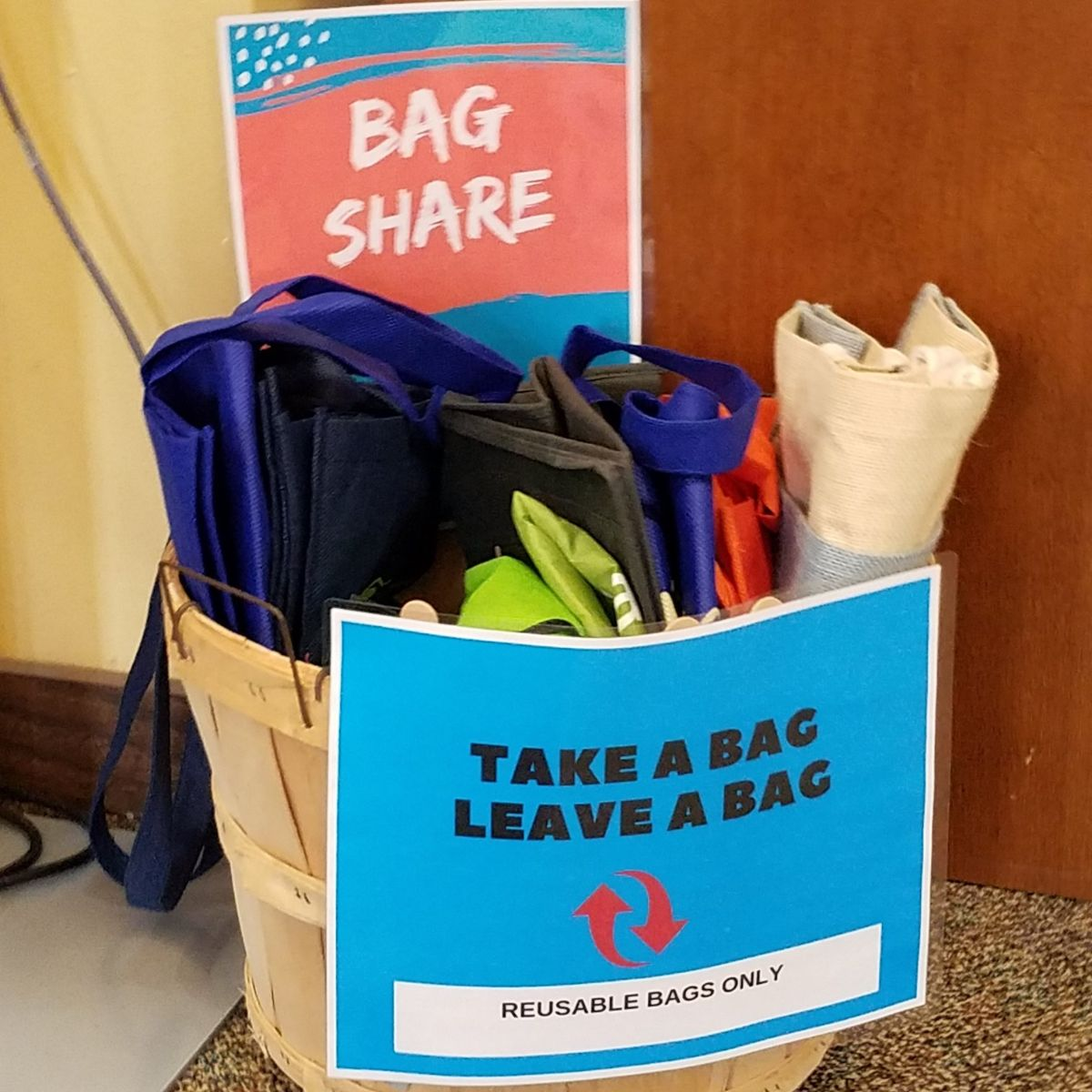 "Basket of reusable bags with sign that says ""Bag Share"""