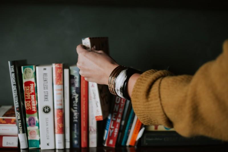 Woman's arm pulling a book off a bookshelf.