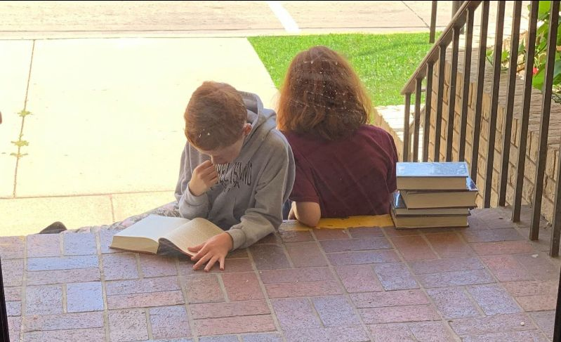 Two children sit on brick steps with stacks of books