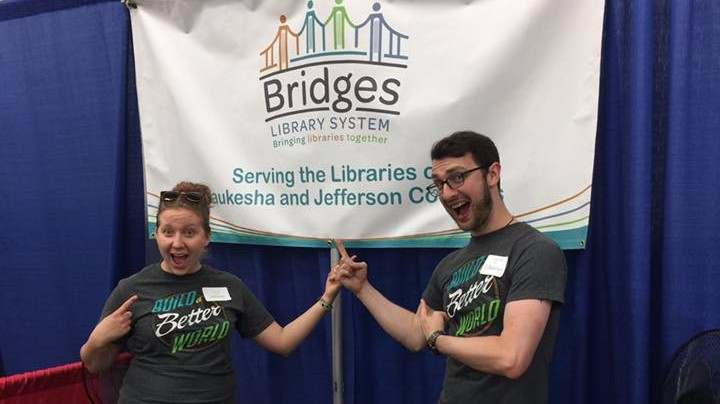 Caitlin and Eric posing at the fair booth with the Bridges Library System banner