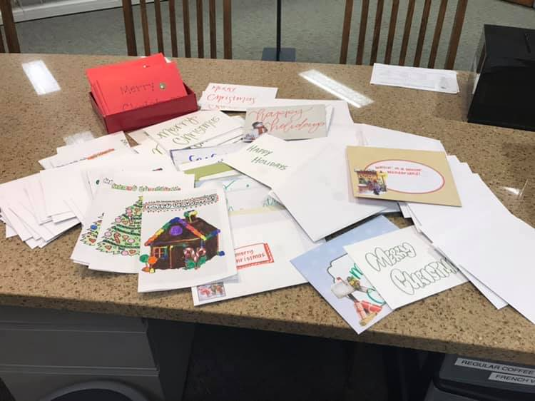 A pile of holiday cards and envelopes on a table