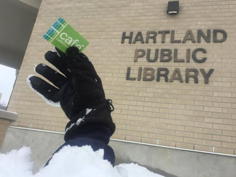 A gloved hand holding a CAFE library card sticking out of the snow, with the Hartland Public Library behind it
