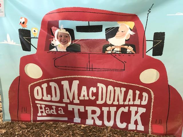 Child peeks through Old MacDonald Had A Truck photobooth banner