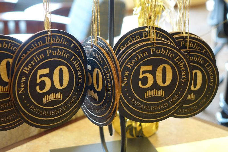 """Ornaments hung on a stand with the New Berlin Public Library """"50 years"""" logo on them"""