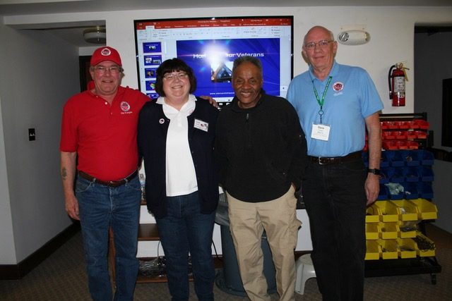 Four people pose for the camera in front of a slideshow