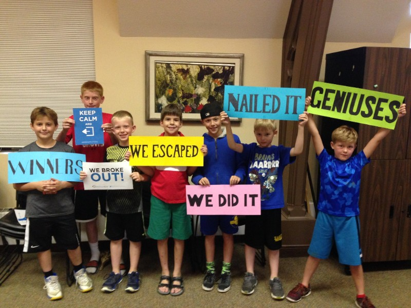 """Group of boys stand together and hold signs that say """"We Escaped"""", """"We Did It,"""" """"Nailed It,"""" etc."""