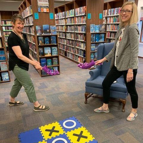 Two women playing games in library