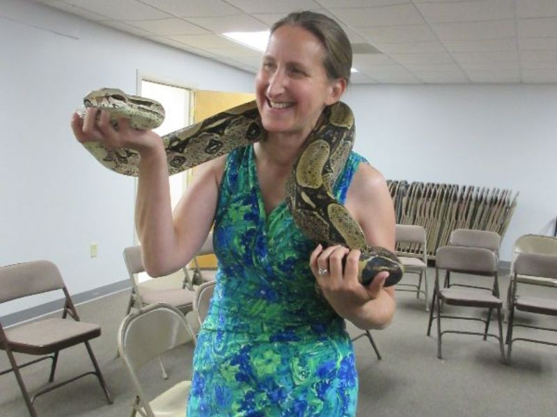 Woman holds snake draped around her neck