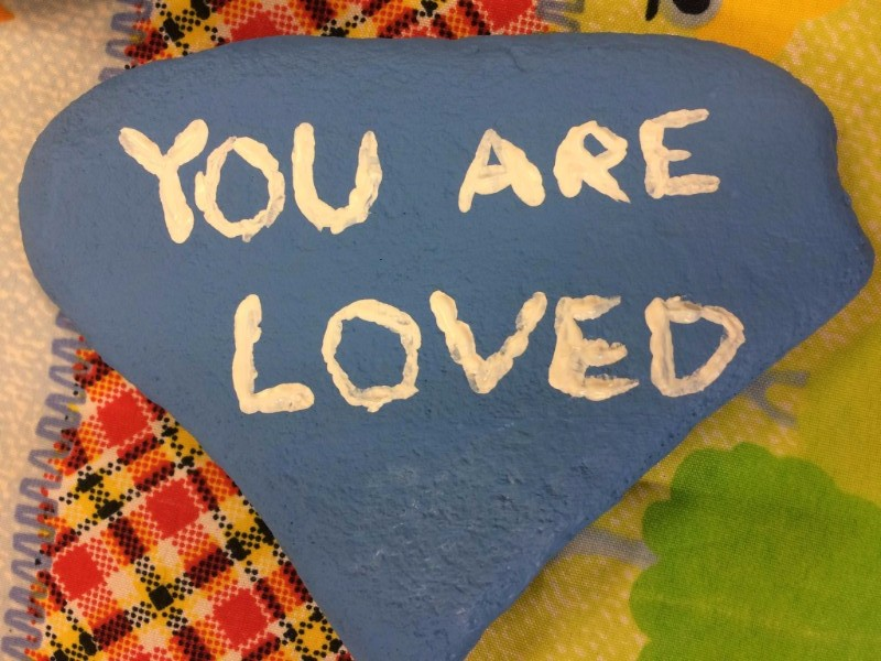 "Blue painted rock with the words ""You Are Loved"" painted on it in white lettering."