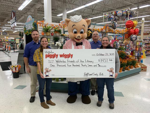 Group of people stand in grocery store with Piggly Wiggly pig mascot holding large decorative check