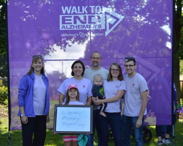 """Five Bridges staff members and two kids standing in front of the """"Walk to End Alzheimer's"""" backdrop, holding a """"Library Memory Project.org"""" sign"""