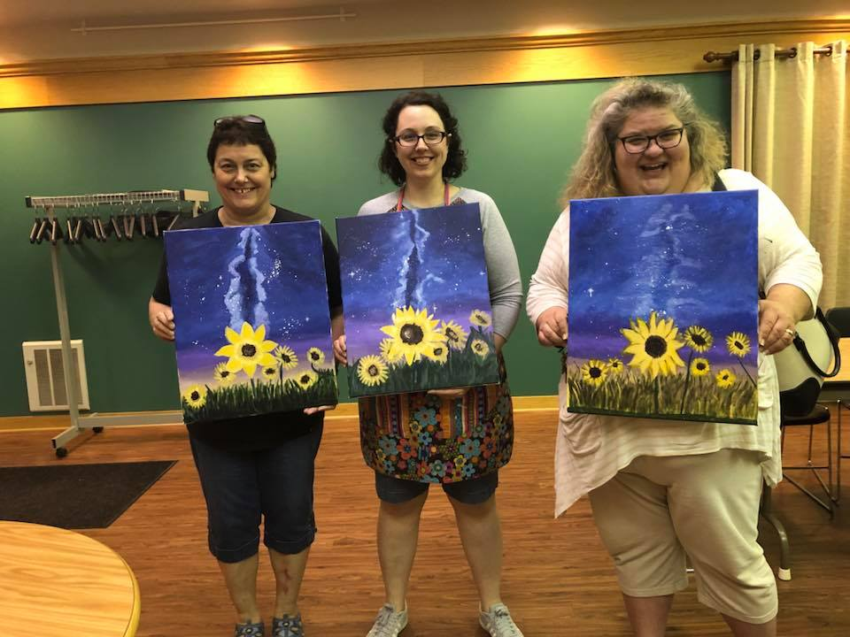 Three women holding paintings of sunflowers