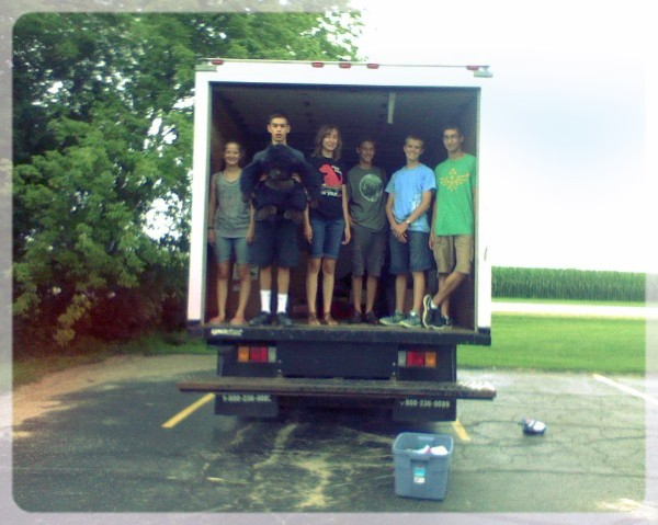 A group of teens standing in the back of a delivery truck