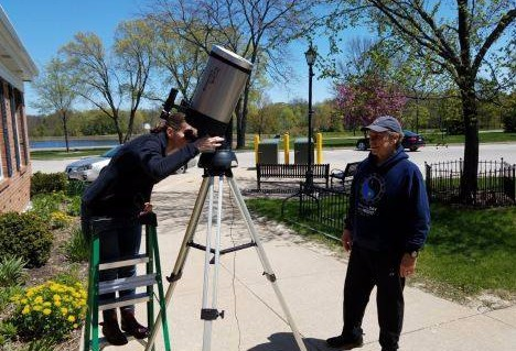 Two people looking through a large telescope outside