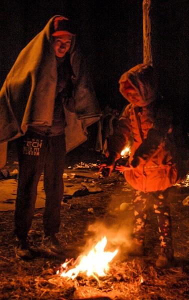 Zwei Flüchtlinge wärmen sich an einem Plastik Feuer