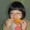 A Chinese lady eating an orange
