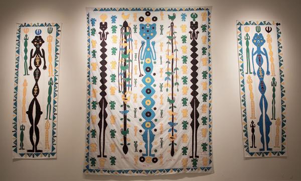 geometric style humanoid figures on printed/sewn wall hangings