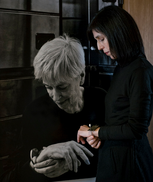 Cristina Filipe wearing a 1980s Bracet of Manuel Machado in front of a picure of Ana Hatherly wering a 1960s bracelet of Kukas. Photo: Eduardo Sousa Ribeiro.  Photo background: C. B. Aragão.