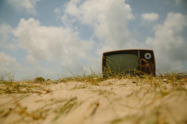 Foto van een ouderwetse tv in een duinlandschap