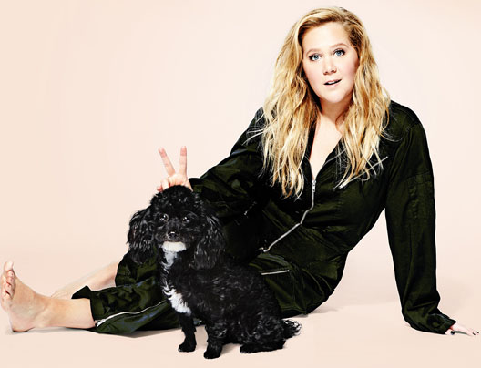 Amy Schumer giving bunny ears to her small black dog.