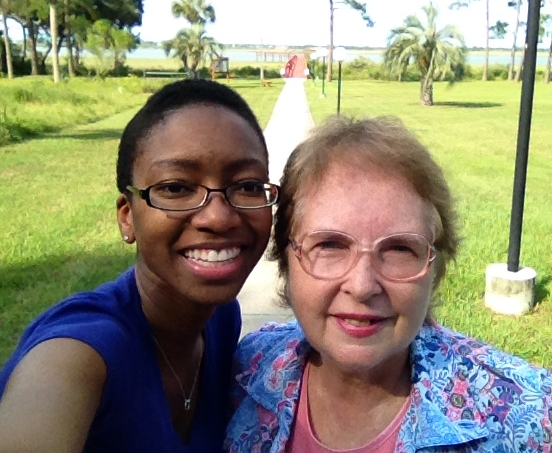 "Founder Talila ""TL"" Lewis in Florida with Mary Ellen, HEARD Advocate for our second eldest #DeafInPrison named Bud (90 years old) #Deaf #Nonagenarian #Prison #ASL  [Image Description: TL w black rimmed glasses and bright purple shirt and Mary Ellen w light rose rimmed glasses and a light blue shirt stand in front of red pier in St. Augustine, Florida. River, trees, grass, sidewalk in the background.]"