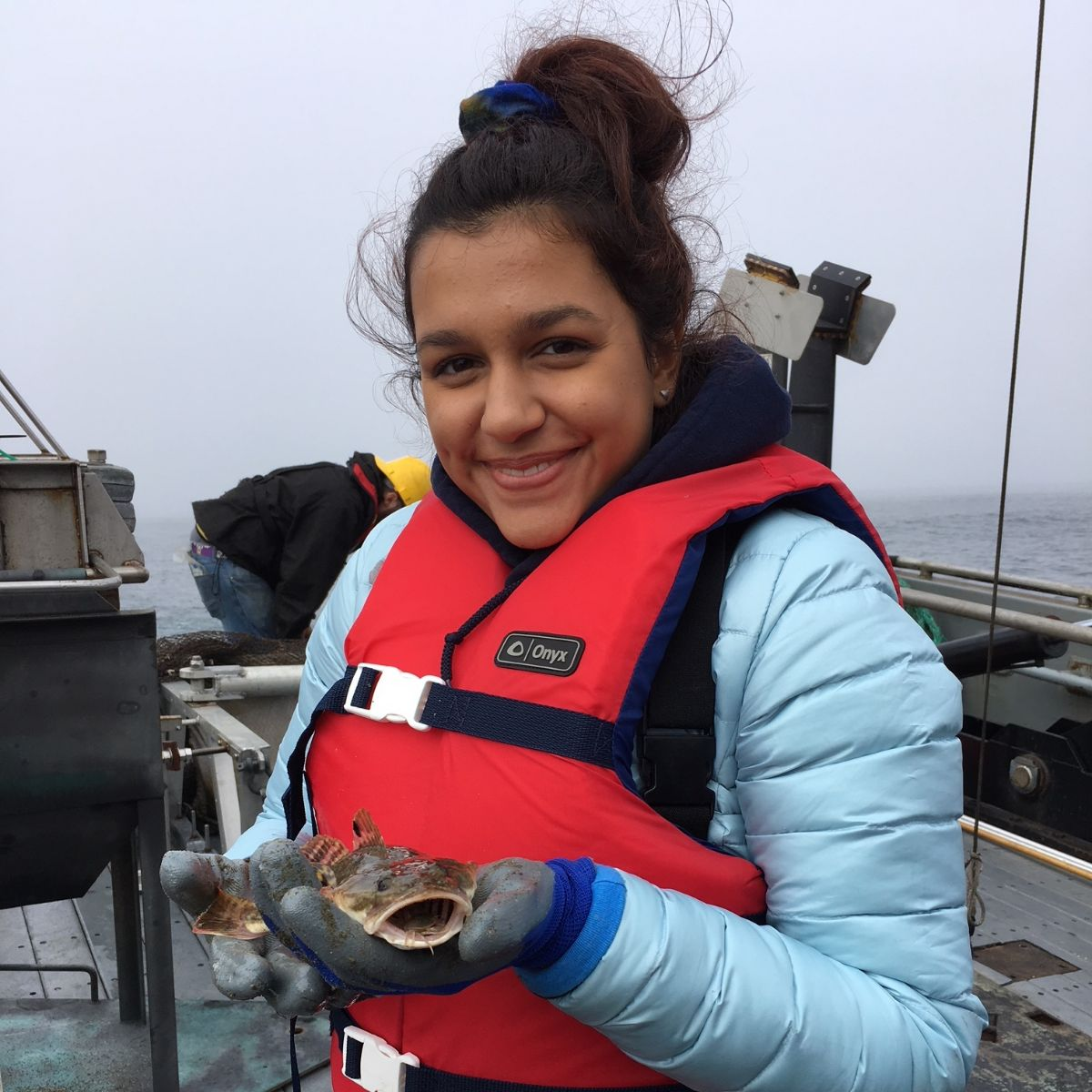 Femal student on a research vessel holding a fish. Photo: Oregon Sea Grant