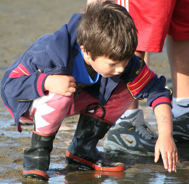 Child in boots crouching down on the mud flat. Photo: Oregon Sea Grant