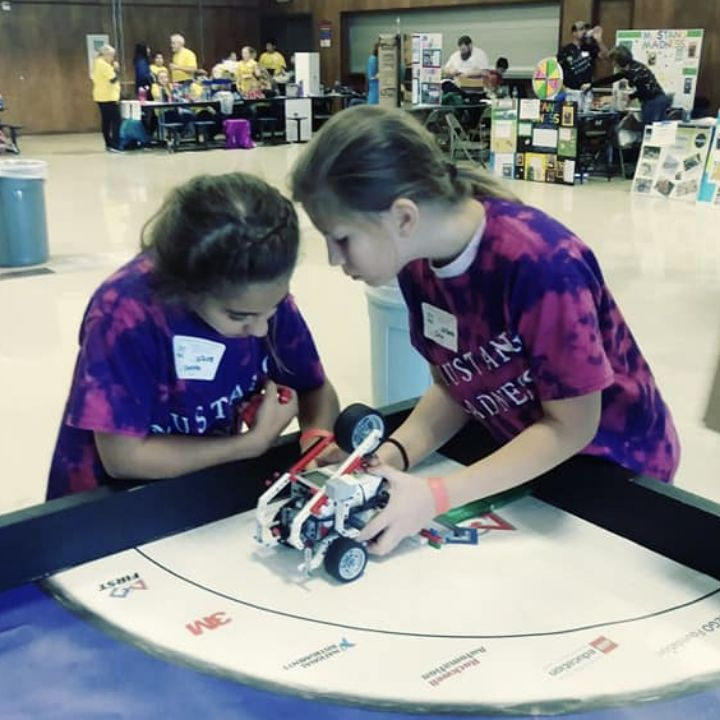 Two Coos Bay students position their LEGO robot on the competition map. Photo: Coos Bay School DIstrict