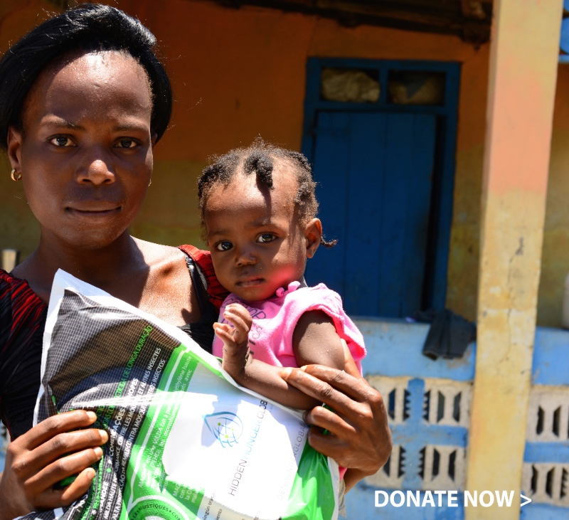 Woman and child in Haiti with a treated mosquito net from HRI.