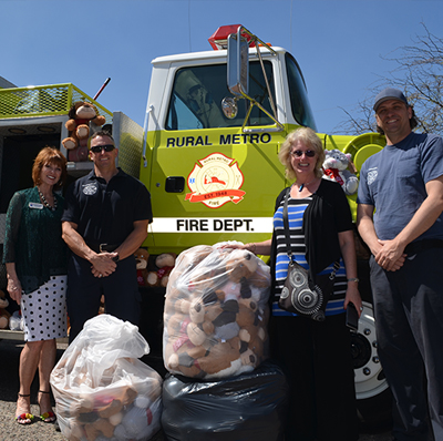 Scottsdale REALTORS® Community Connect Committee members Thomesa Lydon and Julie Goldammer present dozens of stuffed animals to Rural Metro Fire Public Information Officer Shawn Gilleland and Engineer Keith Bunce for children in time of crisis.
