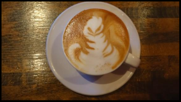 A cappucino with the foam showing a smiling creature