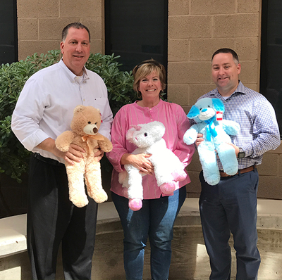 Scottsdale REALTORS®Community Connect Committee member Kim Farrar delivers more than 40 stuffed animals to Sgt. Joe Ferreira (left) and Lt. Patrick Regan (right) atthe Scottsdale Family Advocacy Center.